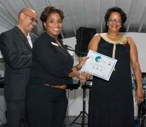 Representative from Vista Rentals accepting Award from the Hon. Yoland Bain Hosford
