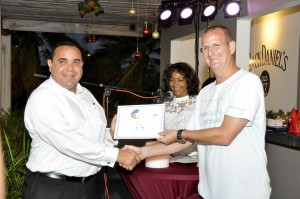 Lieutenant Governor of Bonaire Mr Edison Rijna presenting Award to Bas Noij VIP Diving, Jessica Bensley, CEO Skyviews looks on.